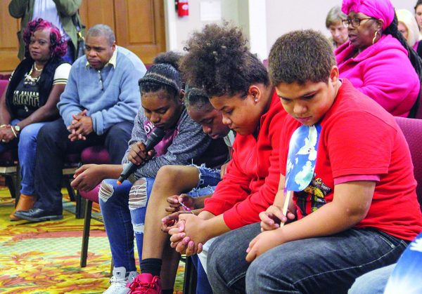 Children bow in preparation for a prayer led by Robert Carpenter, elder of the Carrollton Avenue Church of Christ in New Orleans, during a special Saturday night singing assembly marking the 10th anniversary of the Hollygrove church.
