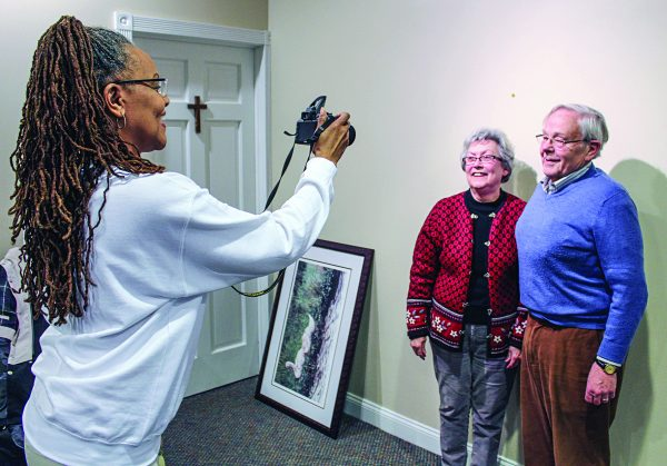 Yvette Curcio, who serves as the church photographer for the newly formed Greenbank congregation, snaps a directory photo of Ed and Brenda Jones.