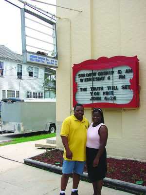 The Marsalises stand outside the Carrollton Avenue Church of Christ, where the main sign still awaited repairs in 2006.