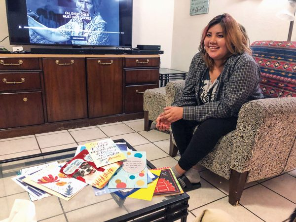 In her family's home, Celeste Lee shows a few of the many cards — encouraging her and congratulating her for graduating — she has received from Christians.