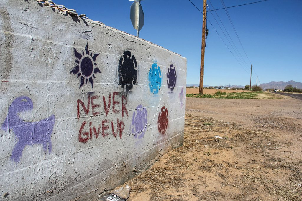 On the Salt River Pima–Maricopa reservation, served by the Salt River Church of Christ, hand-painted messages of encouragement are painted on a roadside barrier.