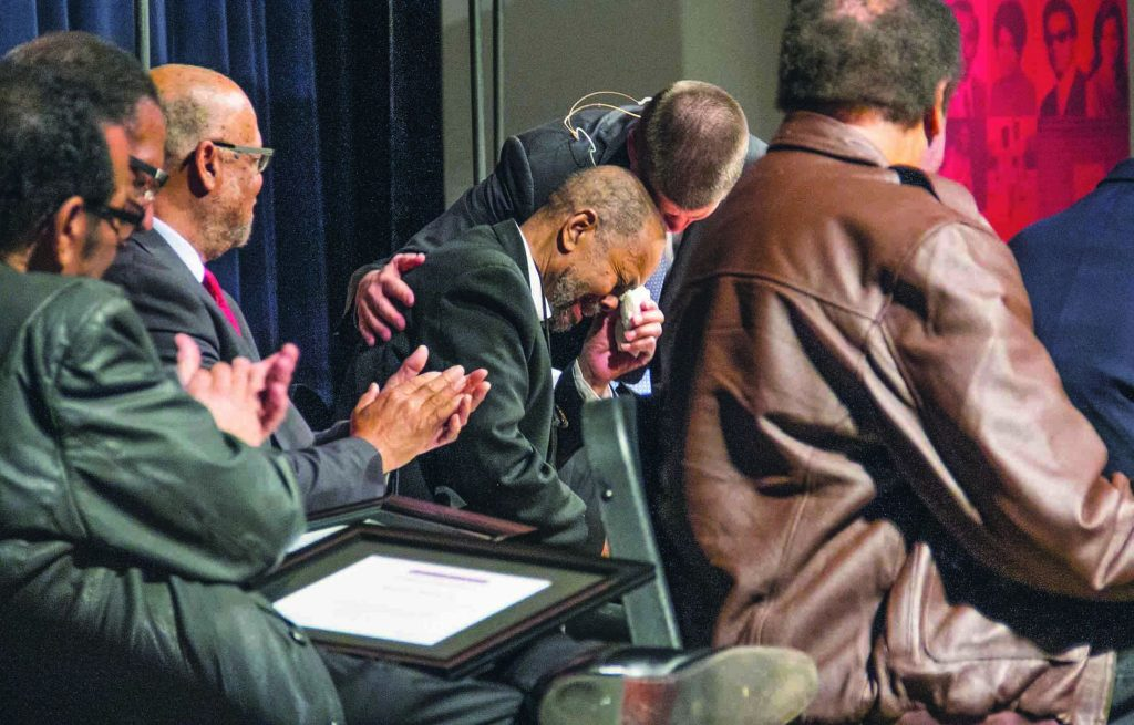 Seated among his classmates, Ron Wright, reacts to a certificate of recognition presented by Oklahoma Christian University President John deSteiguer.