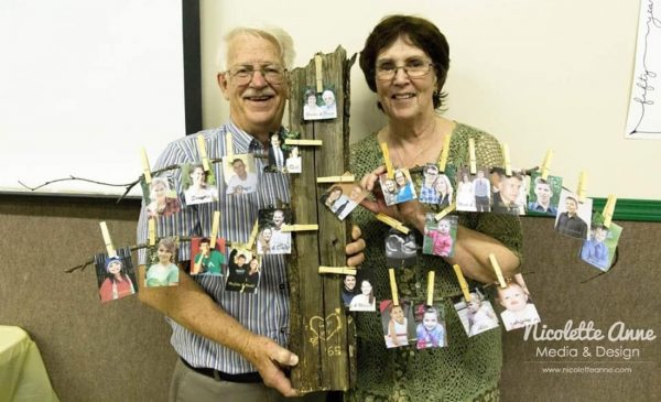 Gordon and Peggy Parmenter hold a family tree diagram.