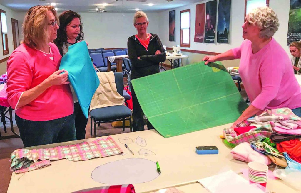 Phyllis Renner, Amy McCumsey and Jenny Lafferty of the North Hills Church of Christ work with Becky Krivak of the Zelienople Church of Christ to make weighted blankets.