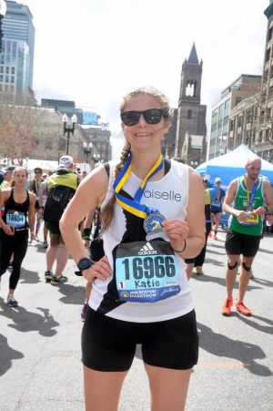 Katie Clark shows her medal after completing the 2019 Boston Marathon.