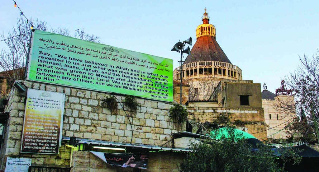 In the city of Nazareth, a billboard bearing a verse from the Quran stands near the steeple of the Basilica of the Annunciation.