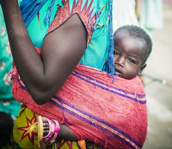 In a rural village in southern Chad, a woman carries a baby on her back.