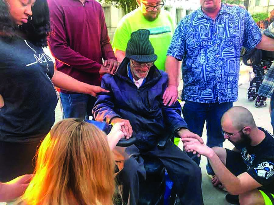 "Members of a spring break DiscipleTrips group pray with Barney, a friend of Central Phoenix Urban Ministry. ""He's been through a lot in life and gave the group advice about how to handle difficulties,"" Sean McClue said."
