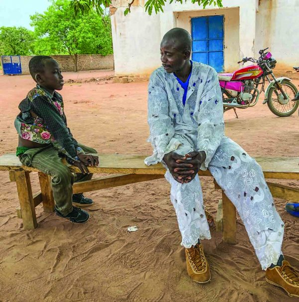 François March talks to his 11-year-old son, Pascal, outside the meeting place of the Dono-Manga Church of Christ in the Central African nation of Chad.
