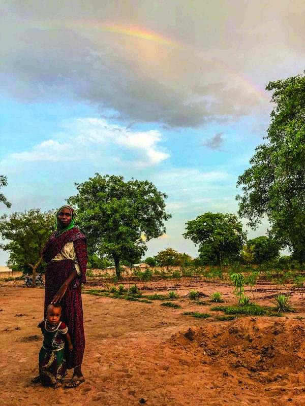 A rainbow forms in storm clouds near Dono-Manga, Chad, as a woman and her child wait for treatment outside the Jordan Health Center.