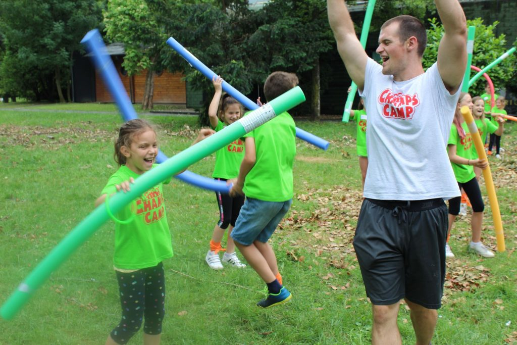 Brady Ross, left, plays with children during Champs Camp in Zagreb, Croatia.