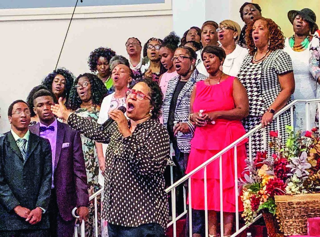 Stacey Wells Young sings with the Electrifying Easternnaires as her mother, Dorothy Wells, seated at far left, directs. The group performed its 50th anniversary concert in Baltimore.