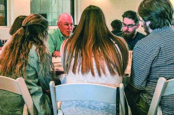 Elder Allen Diles serves as a table leader during Sunday communion, prayer and devotional time.