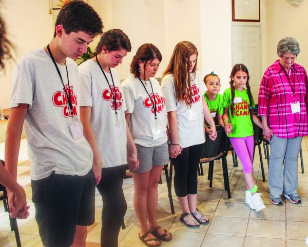 Dylan King, Mary Claire Gunn, Emily Christian and Kathryn Christian from the Crestview Church of Christ in Waco, Texas, pray during Champs Camp in Zagreb, Croatia. At left is Linda Talley, also a Crestview member.