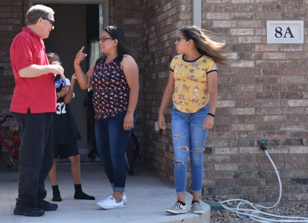 Biatriz Larez visits with Bill Marshall, director of the single-parent family program, outside her duplex at Hope Haven in Portales, N.M.