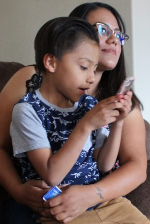 Biatriz Larez holds her 5-year-old son, Zacarias, during an interview with The Christian Chronicle.