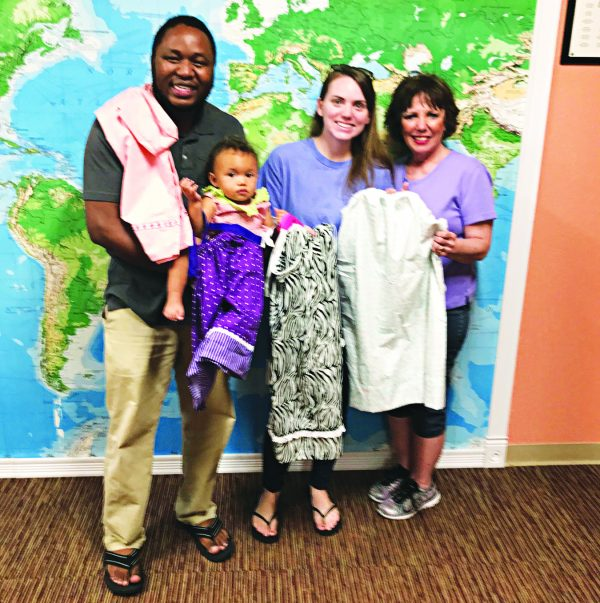 Dagne Seegren Billings presents the dresses to Nkosi, Katie and Tiana Mpofu.