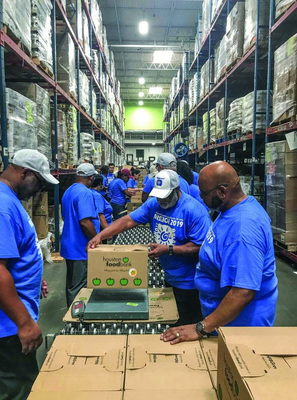 """Volunteers assemble food packages during """"Mission Day 2019"""" in Houston."""