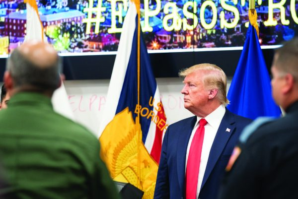 An #ElPasoStrong sign can be seen in the background as President Donald Trump visits the Texas border city after the mass shooting that claimed 22 lives.