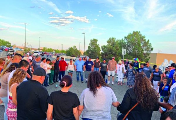 Members of Churches of Christ gather in a circle and hold hands as they pray outside the Walmart in El Paso, Texas, where 22 people were killed Aug. 3.