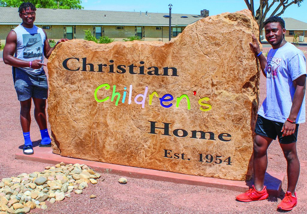 "Philip Blidi and Wromiah ""Romeo"" Gbassagee, both the children of Liberian immigrants, pose by the children's home's sign."