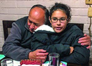 Cici García talks about her exodus from Venezuela and gets a hug from Chilean elder Raúl Fernández.