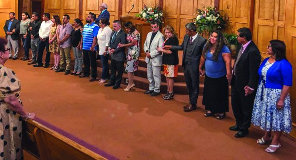 The new elders and deacons and their wives hold hands as they stand in front of the congregation on the Sunday of their installation.