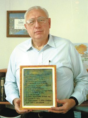 Dan Coker stands in his office in Toluca, Mexico, in 2001 with a copy of Psalm 121 made by one of his students.