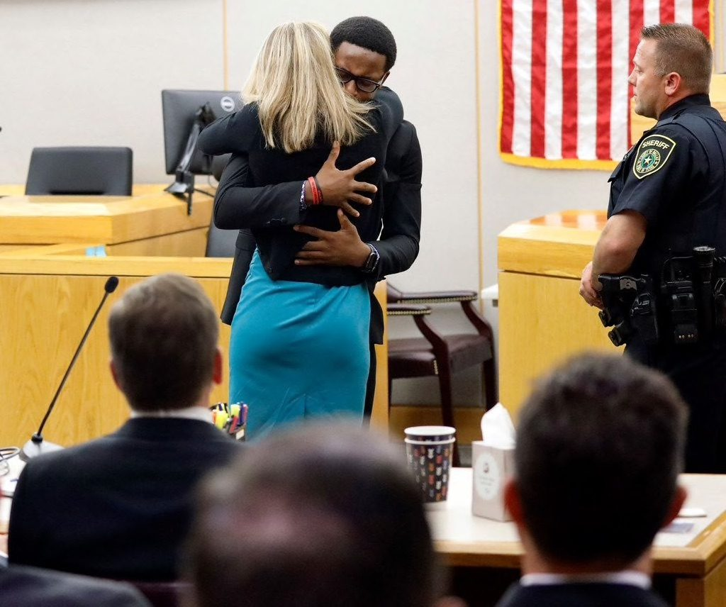 Brandt Jean hugs Amber Guyger in the courtroom following her sentencing for killing his older brother Botham Jean.