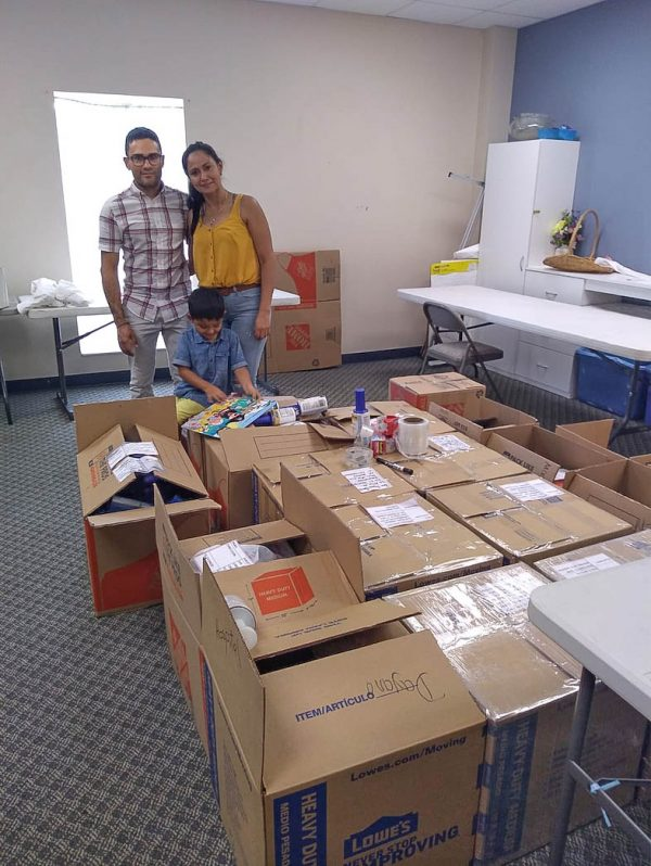 The Yoveras stand next to boxes of supplies destined for Venezuela.