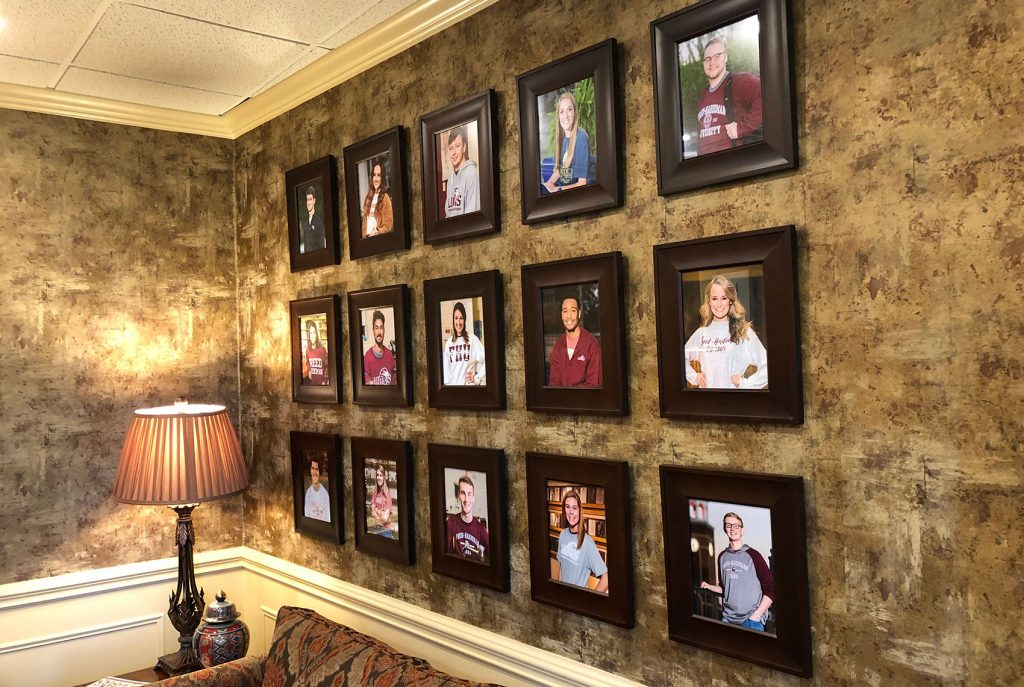 A wall in the presidential offices at Freed-Hardeman University in Henderson, Tenn., shows photos of the university's students.