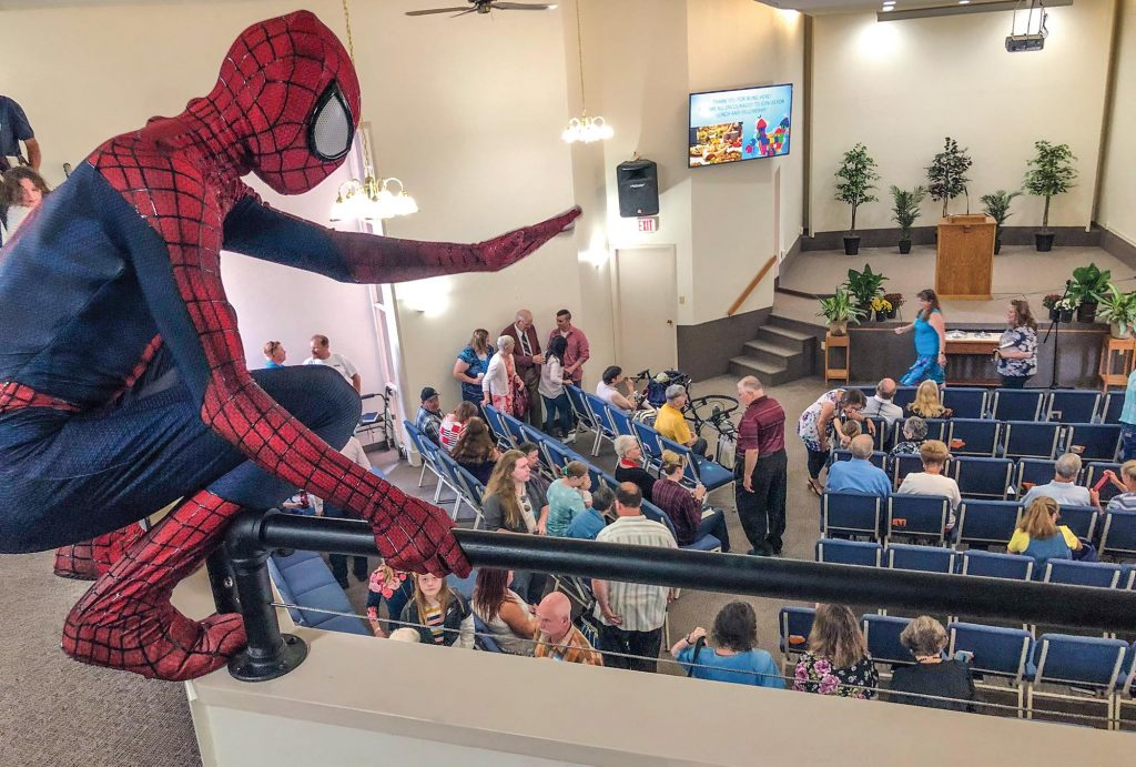 After Sunday worship services, a friendly neighborhood Spider Man invites children to an outdoor carnival and games as the Great Falls Church of Christ celebrates its grand opening.