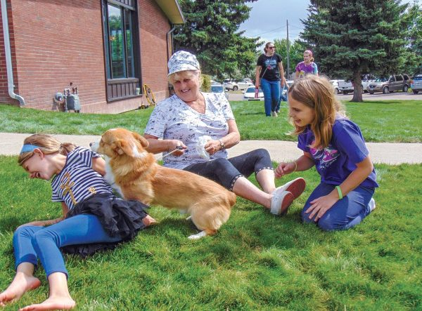 Children are greeted by a friendly canine during the after-worship cookout.