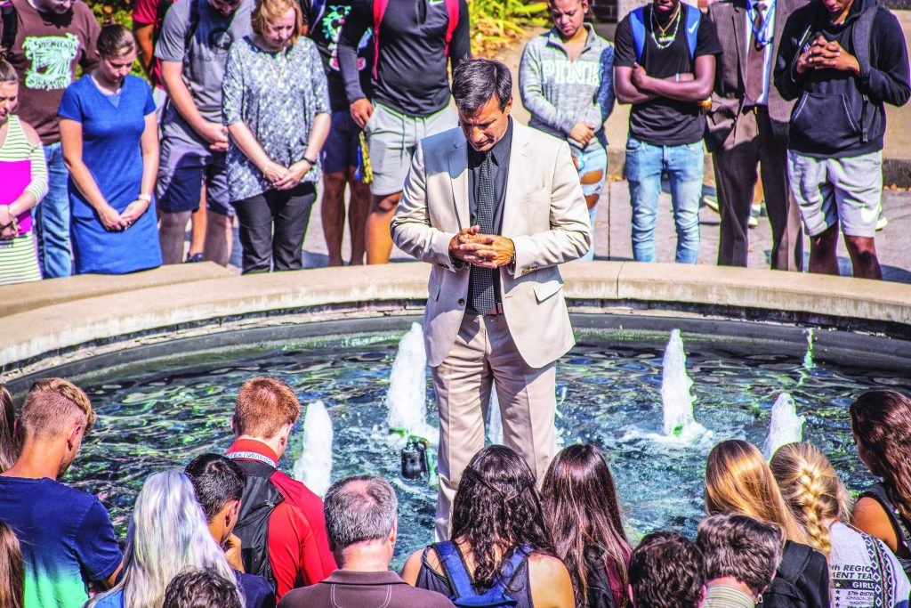 Michael Ross, new president of Ohio Valley University in Vienna, W.Va., prays with students by a campus fountain.