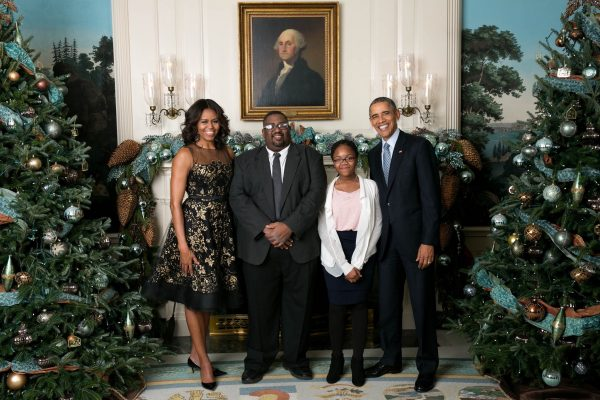 Hamil R. Harris, then a writer for The Washington Post, with his daughter Alana and the Obamas at a White House Christmas party for print media in 2015.