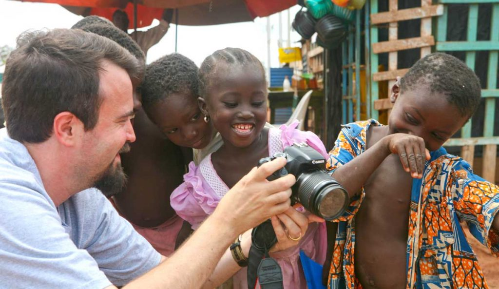 Erik Tryggestad shares a photo and a laugh with children in Burkina Faso.