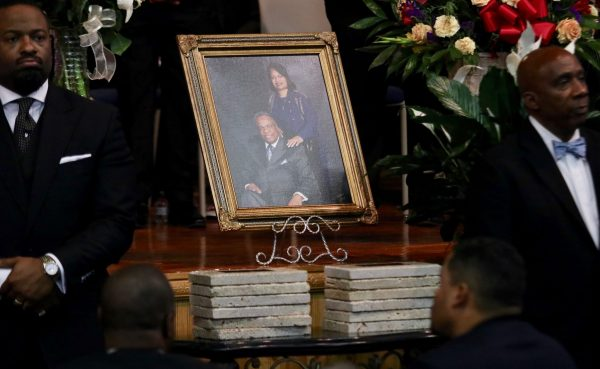 A portrait of Jack Evans Sr. and his wife, Patricia Officer Evans, is shown above 12 memorial stones at the funeral.