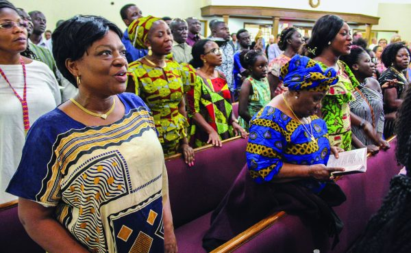 Ghanaian immigrant Christians wear traditional African attire as they worship during the areawide assembly at the Northland church.