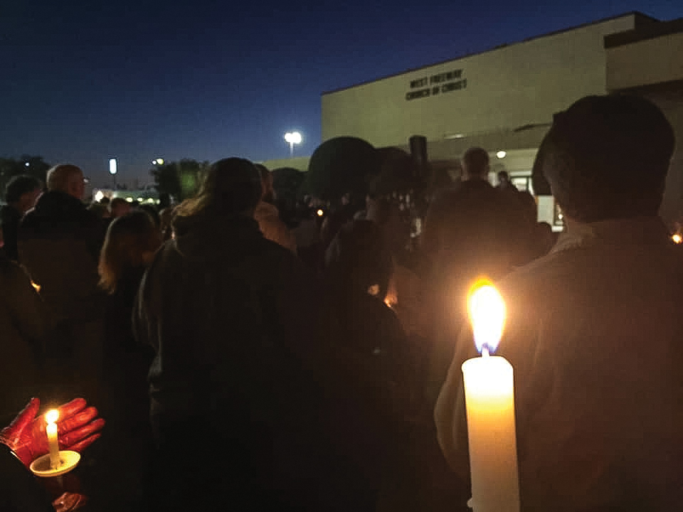 Those grieving the victims of Sunday's shooting hold candlelights outside the West Freeway church building Monday night.
