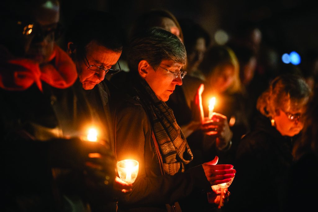 Community members light candles Monday night during a vigil outside the West Freeway Church of Christ building in White Settlement, Texas.