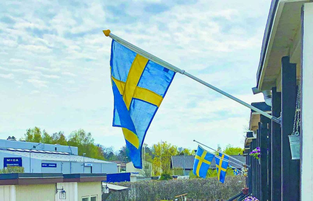 "Swedish flags adorn a row of homes in Åkersberga, a northeastern suburb of Stockholm. The ""Å"" is pronounced a bit like a long ""o."""