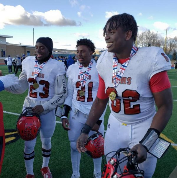 "Wromiah ""Romeo"" Gbassagee, Brandon Blidi and Philip Blidi celebrate Portales High School's state championship."