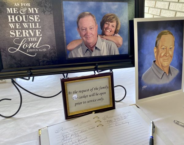 A picture of Richard and Glenda White is seen by the guestbook at Rich White's funeral.