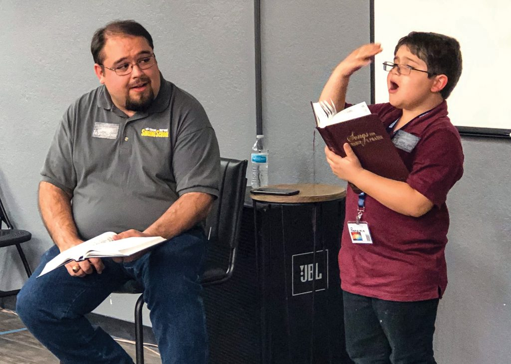 "Benjamin Sisemore, age 6, leads the hymn ""Ten Thousand Angels"" (with a little help from his dad, Levi) during a late-evening devotional in The Well, the campus ministry meeting place for the Sunset Church of Christ in Lubbock, Texas."