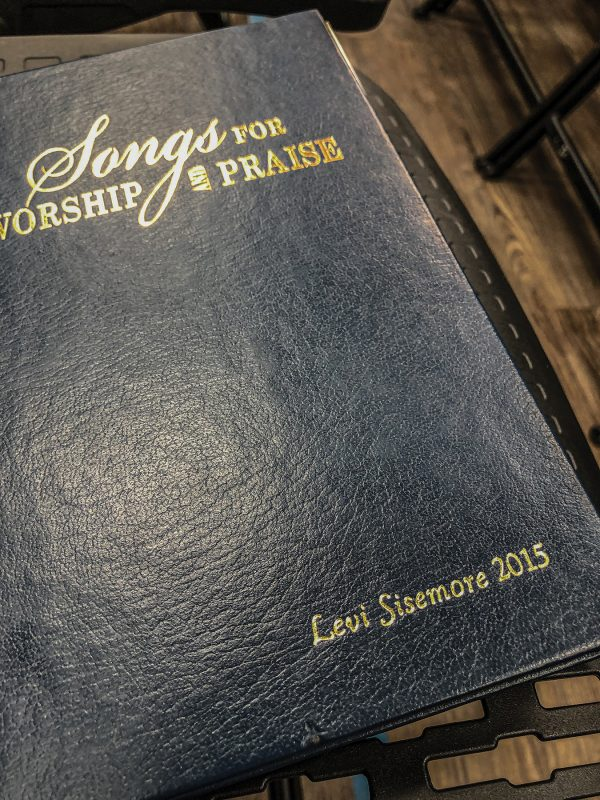 Levi Sisemore keeps a foil-embossed song book from the Texas Normal Singing School.