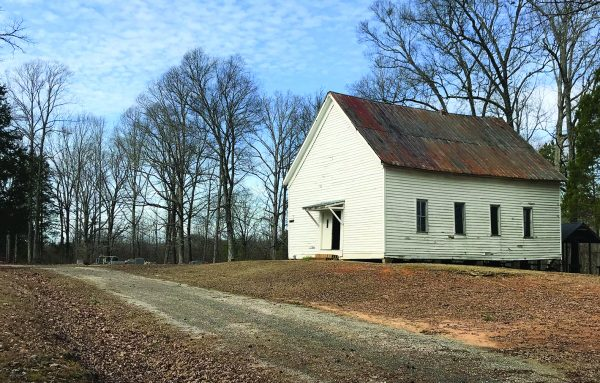 An old white church building with aging wooden benches inside anchors Palestine Cemetery in middle-of-nowhere West Tennessee.