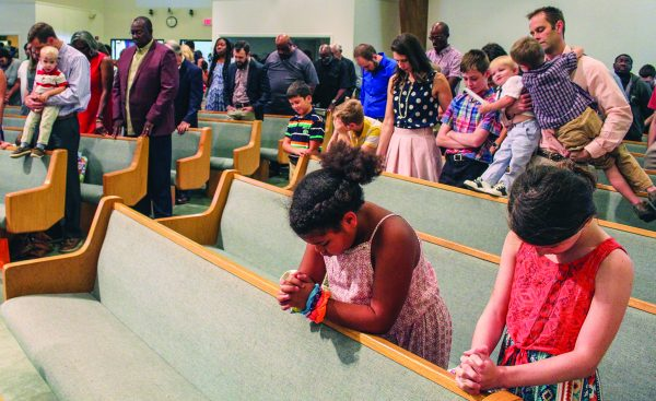 Members of the New York Avenue Church of Christ, including elder Charles Hervey in the maroon suit, pray during a Sunday morning assembly.
