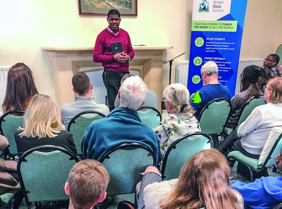 Sola Adeoson gives a communion devotional during the recent British Bible School Winter Family Retreat.