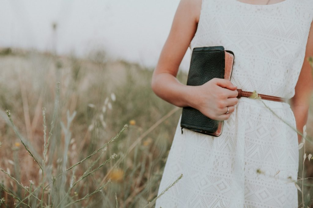 Woman standing in field carrying a Bible in her right hand