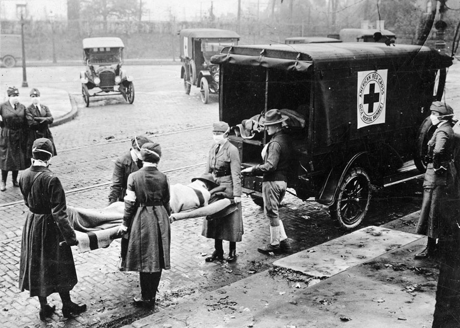 "With masks over their faces, members of the American Red Cross remove a victim of the ""Spanish flu"" from a house in St. Louis in 1918."